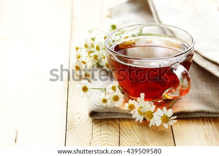 glass cup with tea and chamomile on a wooden background