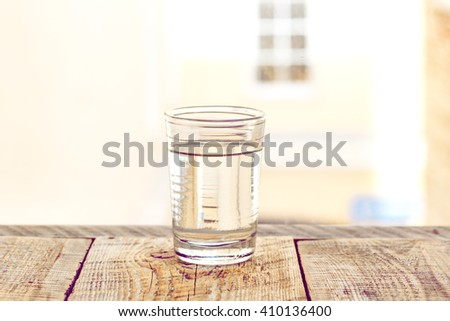 glass cup with water on a background of  window - stock photo