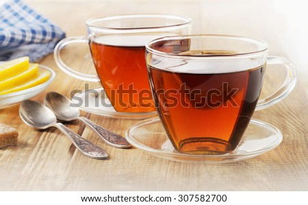 Glass cups of  black tea with lemon. Selective focus - stock photo