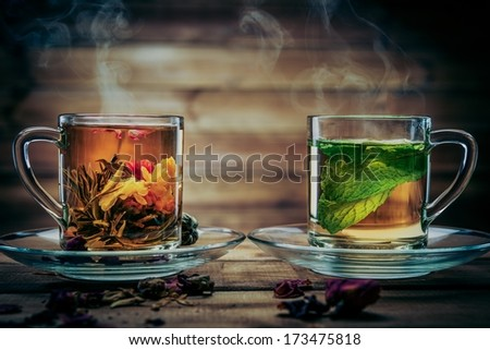Glass cups with tea flower and peppermint tea against wooden background  - stock photo