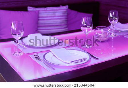 Glass dining table with blue back light in a restaurant - stock photo