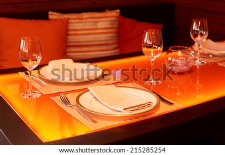 Glass dining table with orange backlight in a restaurant - stock photo