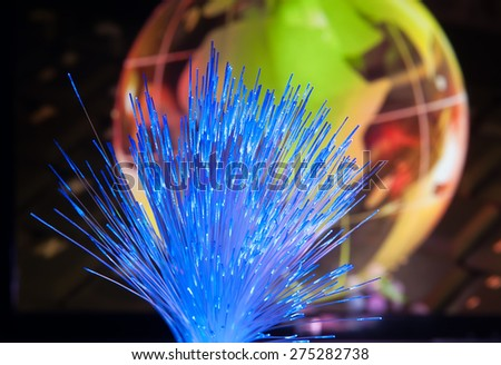 glass earth with network against fiber optic background - stock photo
