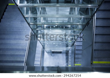 Glass elevator shaft and concrete staircase leading down towards an underground train station in Vienna, Austria. - stock photo