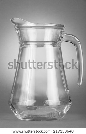 Glass, empty jug on sport gray background