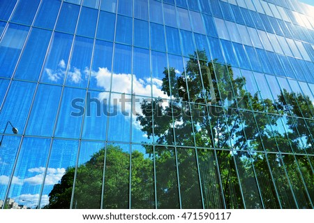 Glass exterior facade of urban building tree reflection.