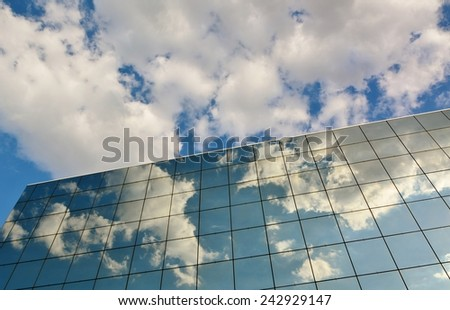 Glass facade of modern office building with reflection of blue sky and clouds.