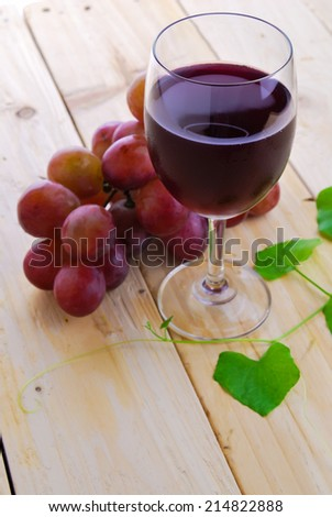 Glass filled with Red Grape Juice  and ripe sweet grape fruit on wooden plank table