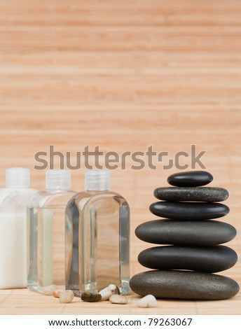 Glass flasks with pebbles  and a black stones stack against bamboo background