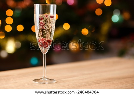 Glass full of champagne with cranberries on table - stock photo