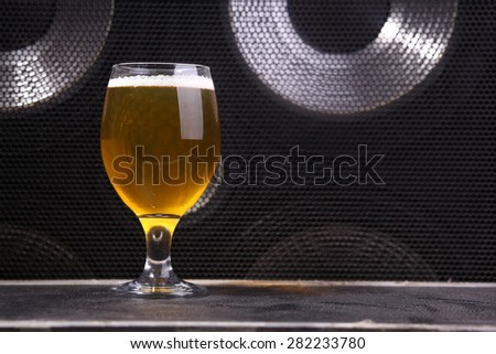 Glass full of light beer standing on a music equipment crate near a big grilled music monitor - stock photo