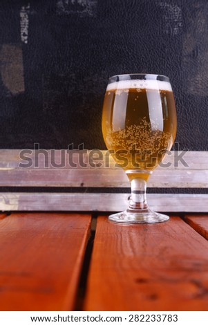 Glass full of light beer standing on a wooden table with a music equipment case in the background