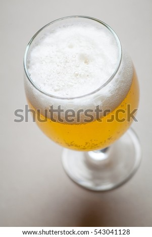 Glass full of light lager beer standing on a gray table
