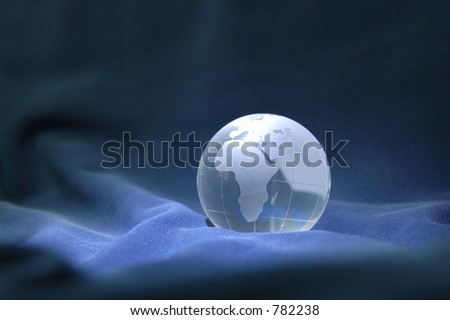 Glass globe against blue velvety background - stock photo