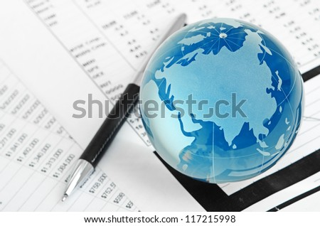 Glass globe and pen on finance