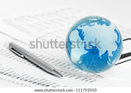 Glass globe and pen on finance background