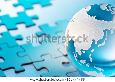Glass globe and unfinished puzzle. Closeup of glass globe. Showing Asia.  - stock photo