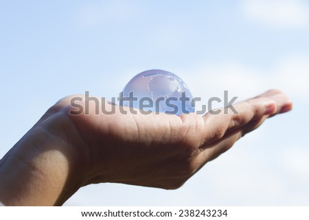 Glass globe in hand  on sky background concept for environment - stock photo