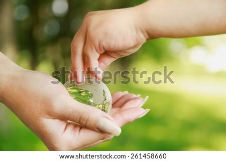 Glass globe in hands - stock photo