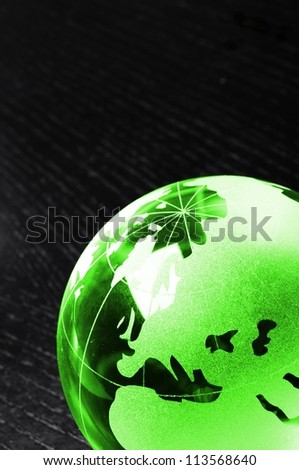 glass globe on black background showing business or environment concept with copyspace - stock photo