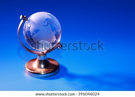 Glass globe on blue background with free space
