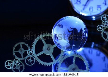 Glass globe on dark background with clock dial and gears