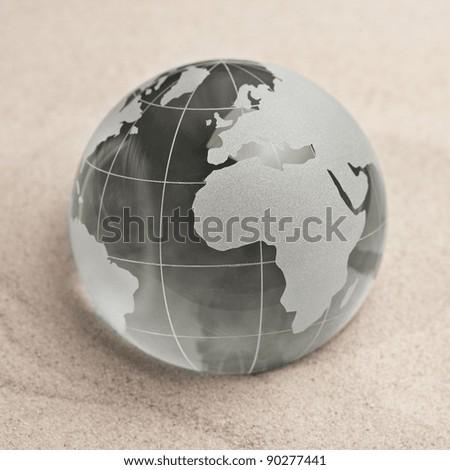 Glass globe on sand background - stock photo