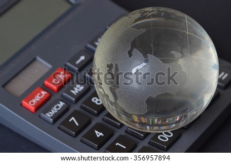 Glass globe with calculator on black background