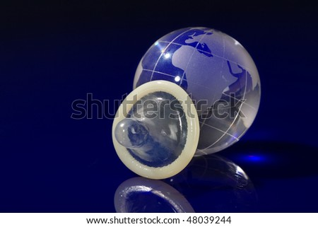 Glass globe with condom on blue background - stock photo