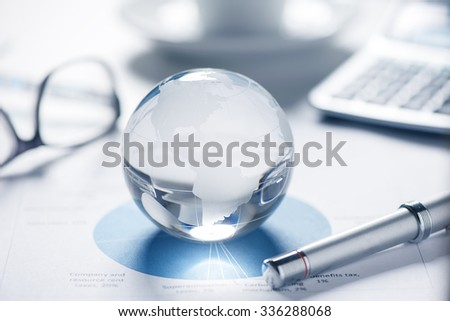 glass globe with stock charts and calculator  - stock photo