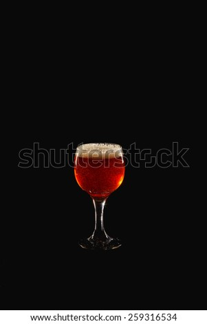 Glass goblet on a black background. In a glass of beer or wine is poured. Jet of liquid fills the glass. A glass of dark honey beer. Amber glass of wine. Pour into a glass, pour a full. - stock photo