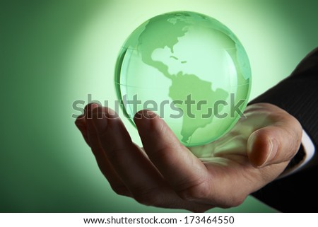 Glass green globe glowing in palm of businessmans hand - stock photo