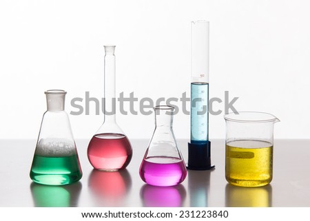 Glass in a chemical laboratory filled with colored liquid during the reaction  - stock photo