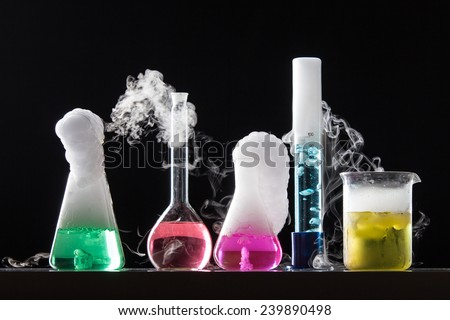 Glass in a chemical laboratory filled with colored liquid during the reaction - studio shoot - stock photo