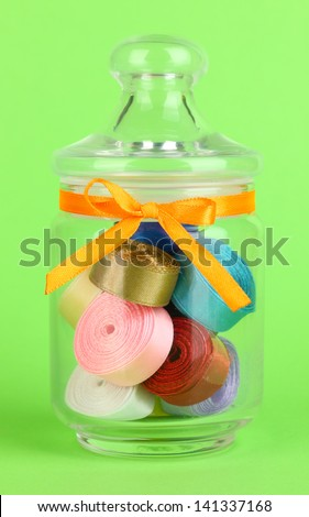 Glass jar containing various colored ribbons on green background - stock photo