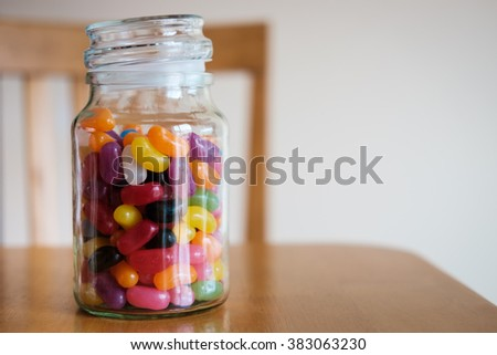 Glass jar filled with jellybeans, lid open and sitting on table with chair in background. - stock photo