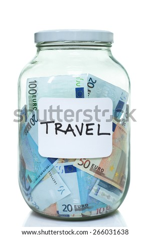 Glass jar full of Euro with a label that says travel - stock photo