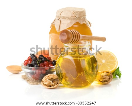 glass jar full of honey, lemon and berry isolated on white background - stock photo