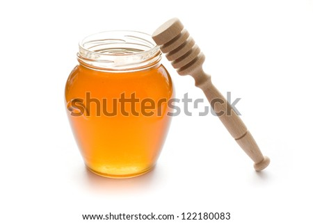 Glass jar full of honey with stick isolated on white background