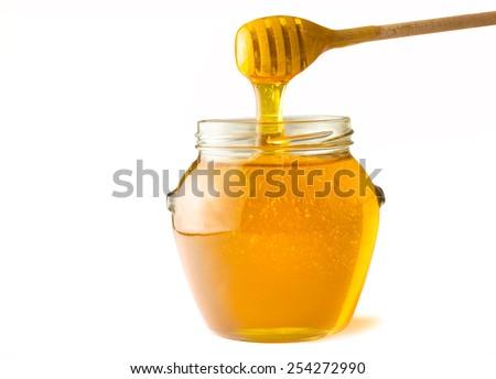 Glass jar full of honey wooden honey dipper - stock photo