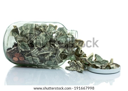 Glass jar full of money tipped over on its side spilling money with lid - stock photo