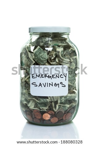 Glass jar full of money with a white emergency savings label - stock photo