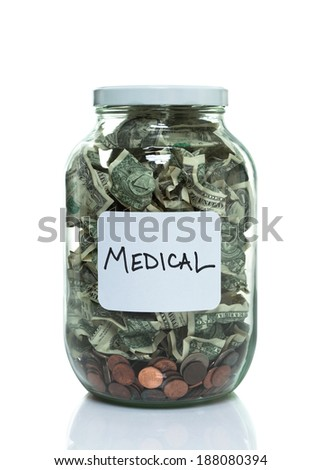Glass jar full of money with a white medical label - stock photo