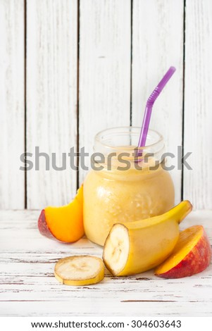 Glass jar of fresh homemade smoothie with banana and peach.