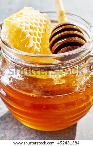 Glass jar of fresh honey with a piece of healthy wax honeycomb and a wooden dipper or dispenser in a close up view - stock photo