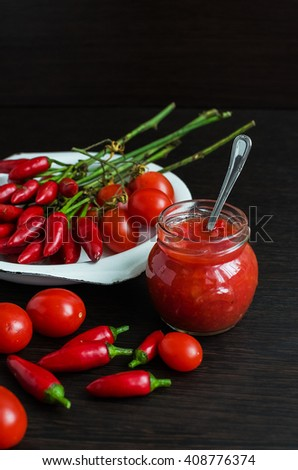 Glass jar of homemade tomato sauce with fresh ingredients on dark wooden background. Natural homemade sauce of tomatoes, peppers and vegetables. Chilli jam. Selective focus.  - stock photo