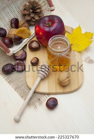 Glass jar of honey with apples, chestnuts and walnuts on a wooden background  - stock photo