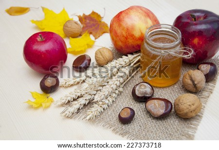 Glass jar of honey with apples, ears of wheat, chestnuts and walnuts on a wooden background