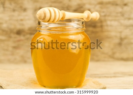 glass jar of honey with drizzler on wooden background - stock photo
