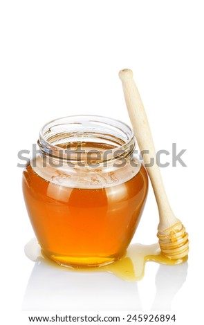 Glass jar of honey with wooden drizzler on a white background. - stock photo